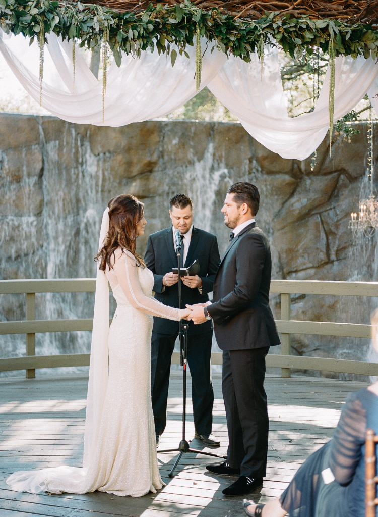 Vows under arch with waterfall