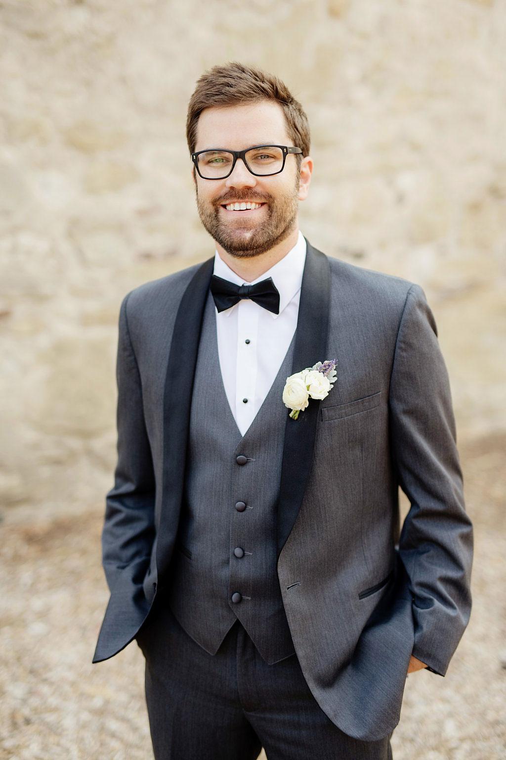 Groom in custom black suit at Serra Plaza wedding.