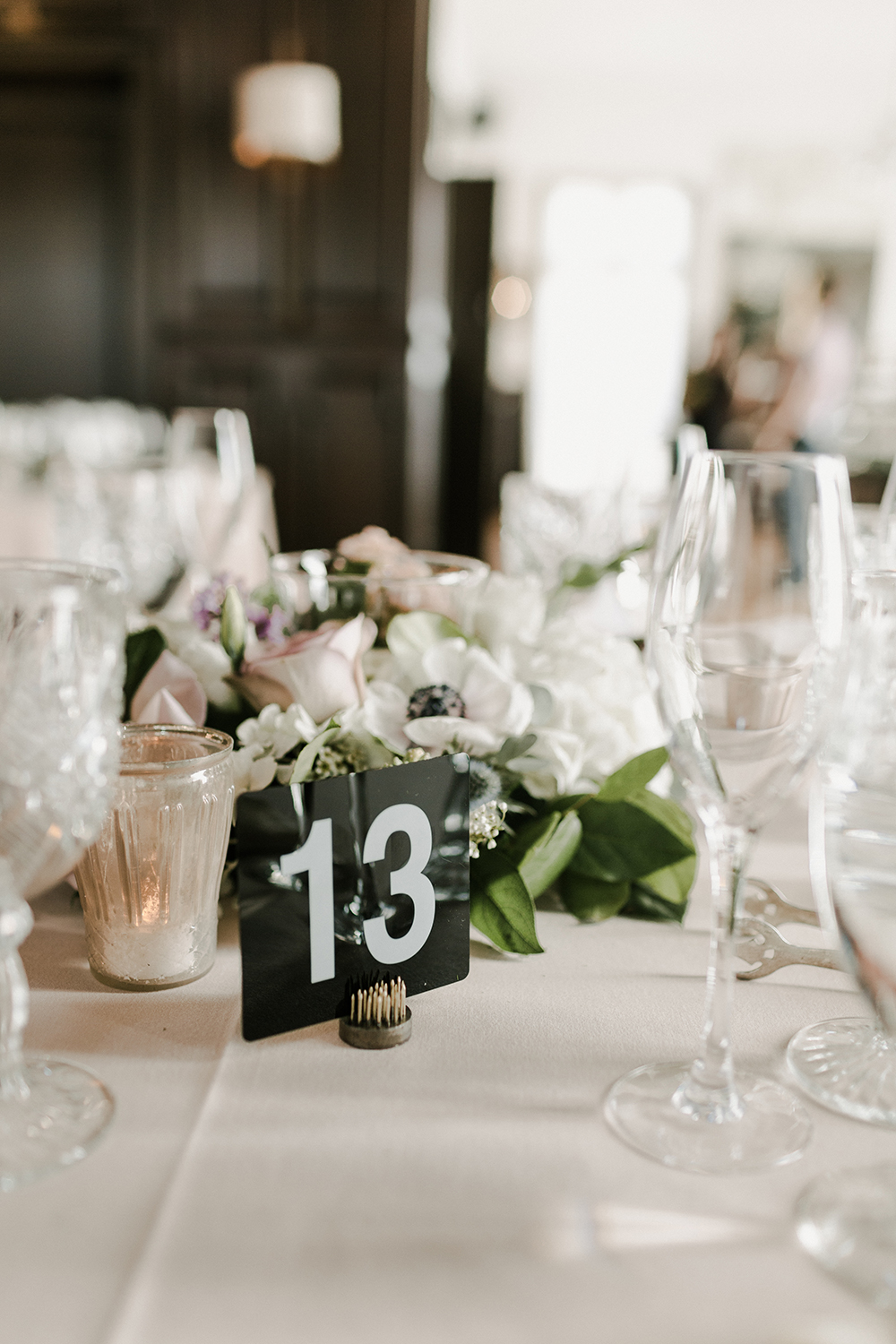 Modern typeface table number on a brass frog at a moody Ebell of Long Beach wedding