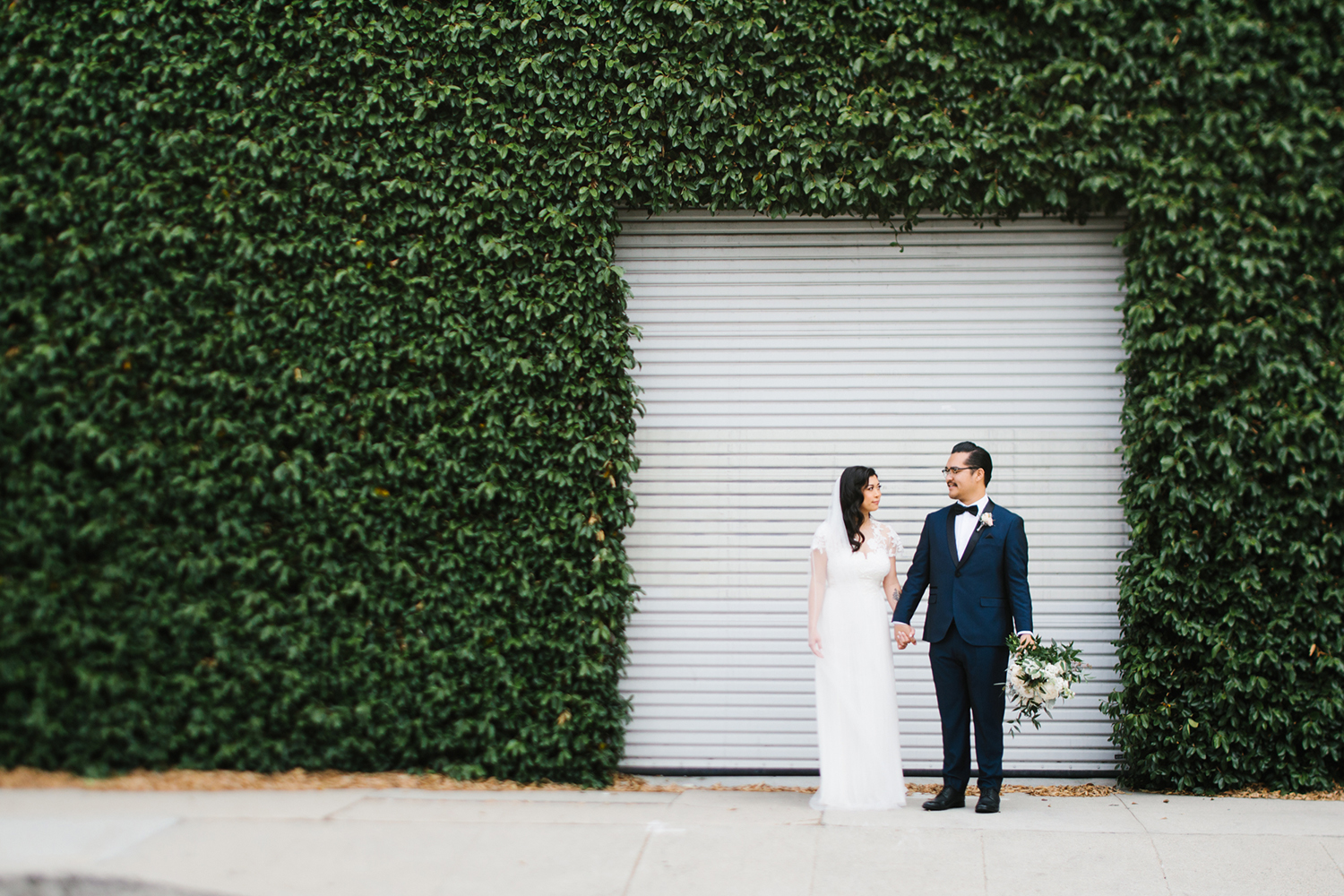 Bride and groom portraits in front of green wall