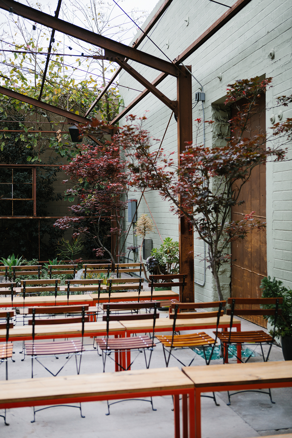 Modern ceremony seating with bistro benches and metal chairs.