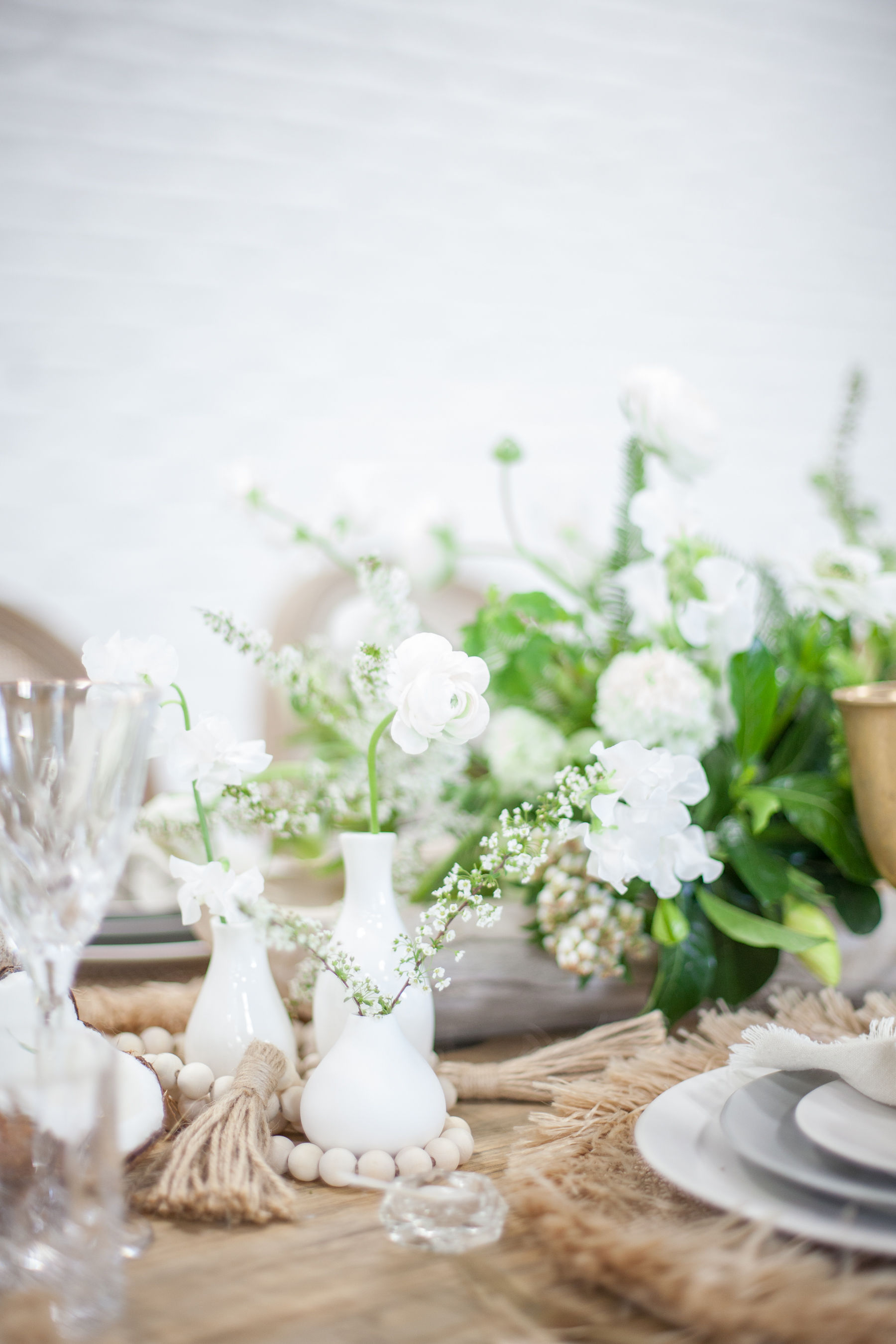 White bud vases with minimal white flowers.