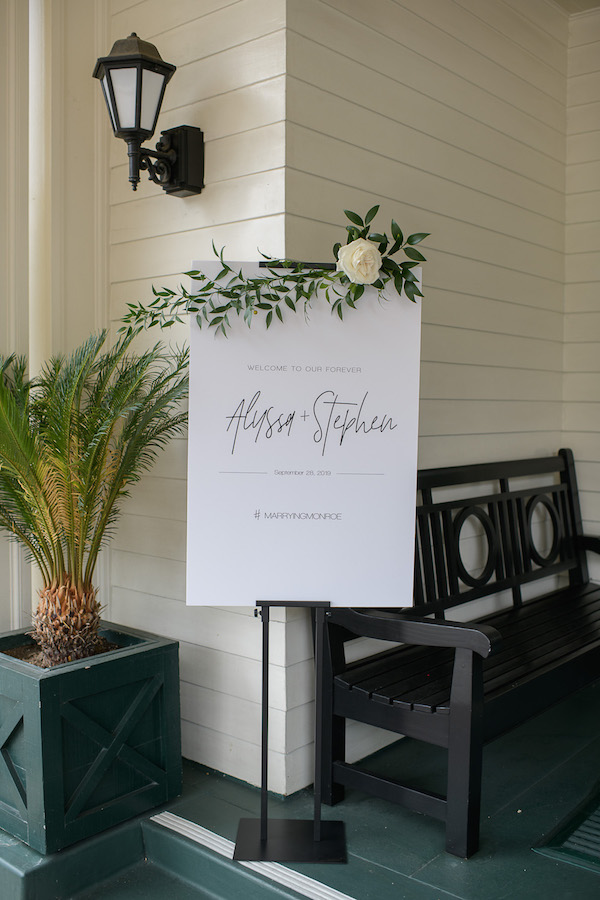 Black metal sign holder for weddings. Adjustable for any size available for rental through Lucky Day Events Co