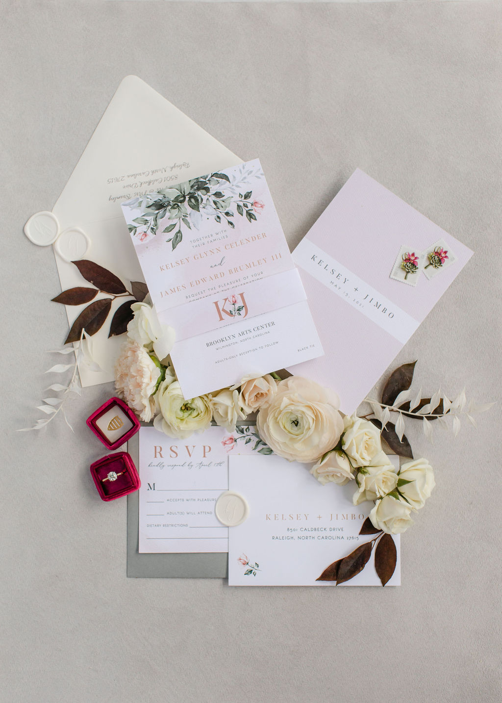 Invitation suite styling with pinks, greens and white florals